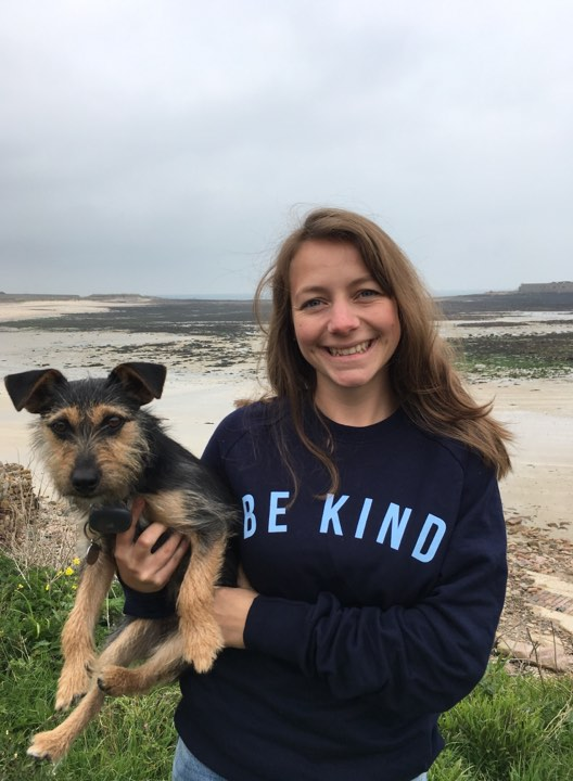 Vet Joanna Woodnutt holding dog with beach in background